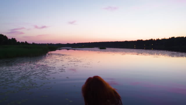 vidéos et rushes de young woman in red dress walks to river and enjoys vivid crimson sunset during summer solstice - robe rouge