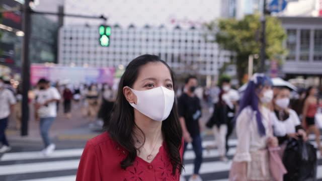 赤いドレスを着た若い女性が保護フェイスマスクを着用し、渋谷十字の上を歩く - 赤のドレス点の映像素材/bロール