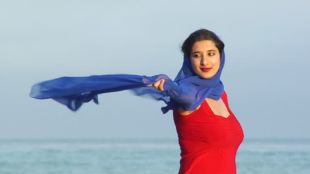 SLO MO, MS, Young woman in red dress with blue scarf blowing in wind on beach, Los Angeles, California, USA