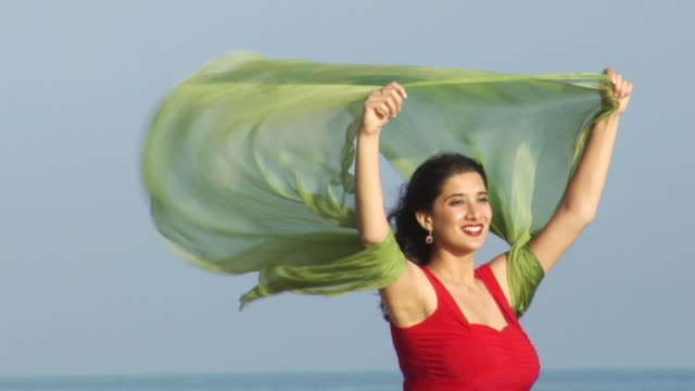 vidéos et rushes de slo mo, ms, young woman in red dress with green scarf blowing in wind on beach, los angeles, california, usa - robe rouge