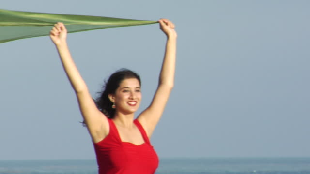 vidéos et rushes de slo mo, ms, pan, young woman in red dress with green scarf blowing in wind on beach, los angeles, california, usa - robe rouge
