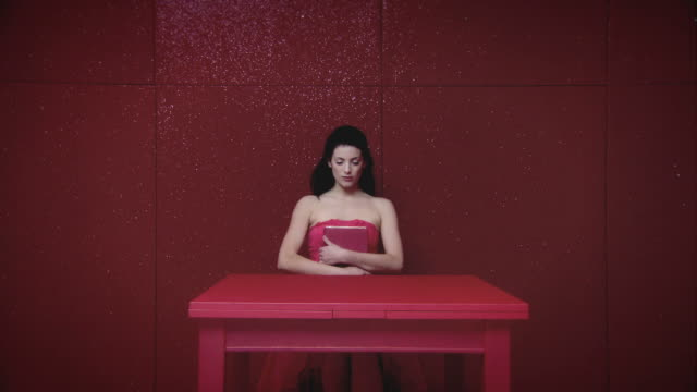 Young woman in red room with book
