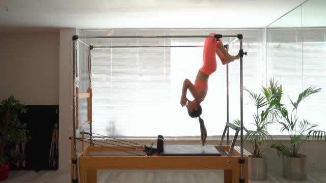 junge frau in reformer fitnessübung - schwingen stock-videos und b-roll-filmmaterial