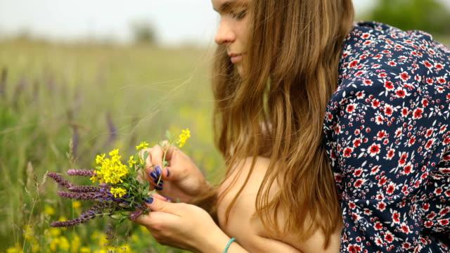 vidéos et rushes de jeune femme dans la robe rustique rassemblant le pavot et les fleurs sauvages dans la lumière de coucher du soleil, marchant dans le pré d'été - bouquet de fleurs