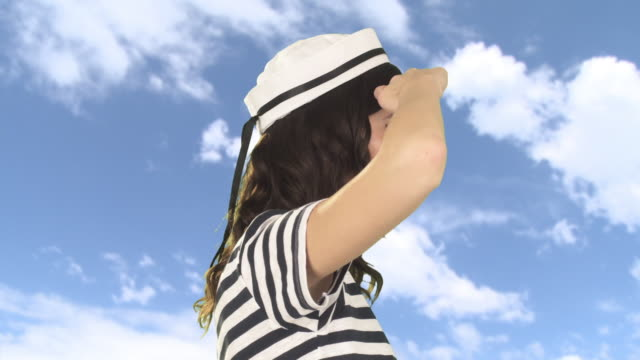 young woman in sailor hat looking away - 手をかざす点の映像素材/bロール