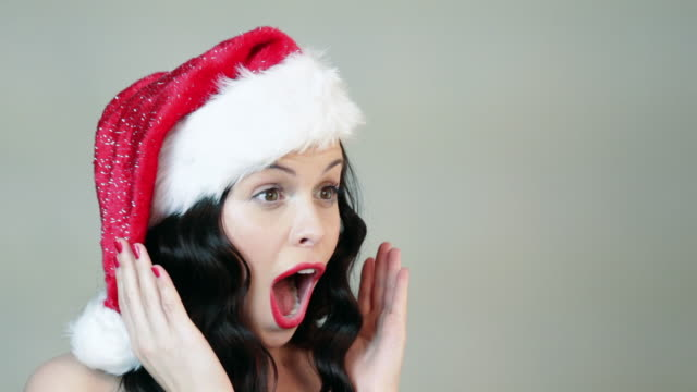 Young woman in santa hat being surprised