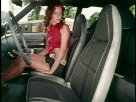 MONTAGE Young woman in shorts getting into 1973 AMC Gremlin and rubbing hands over the Levi's brand trim interior/ USA