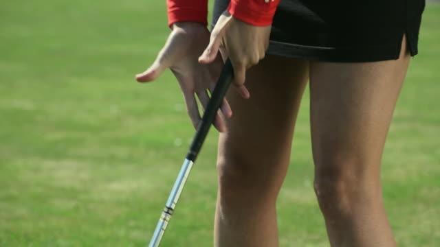 CU Young woman in shorts hitting golf ball / Canterbury, Kent, UK