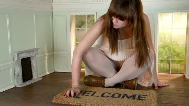 young woman in small house with key and welcome mat - welcome mat stock videos & royalty-free footage