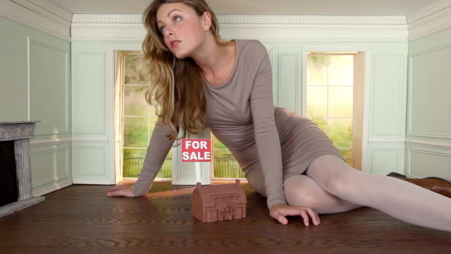 young woman in small house with model house and for sale sign - dollhouse stock videos & royalty-free footage