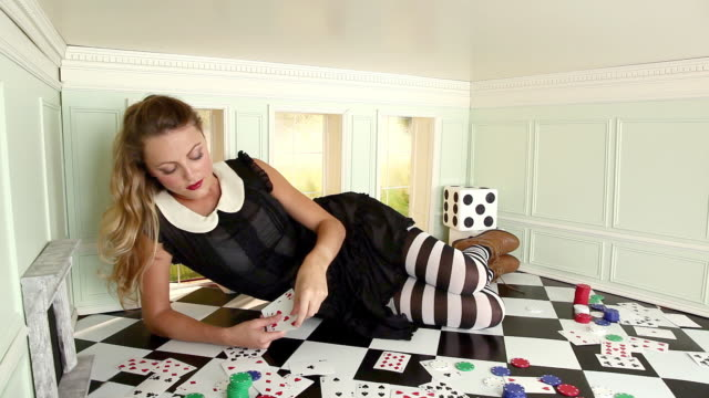 young woman in small room throwing playing cards - alice in wonderland stock videos and b-roll footage