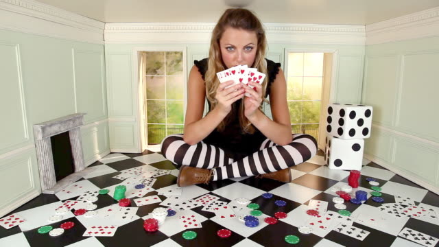 young woman in small room with playing cards, poker chips and dice - alice in wonderland stock videos and b-roll footage