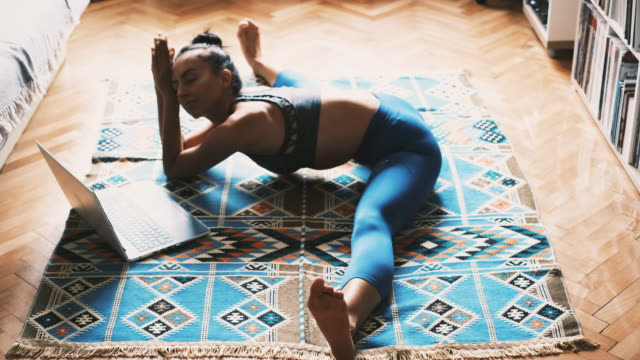 young woman in sports clothing doing the splits while exercising at home - doing the splits stock videos & royalty-free footage