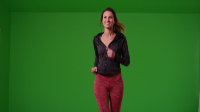 vídeos y material grabado en eventos de stock de young woman in sports wear jogs toward the camera while smiling on green screen - inserción de imagen