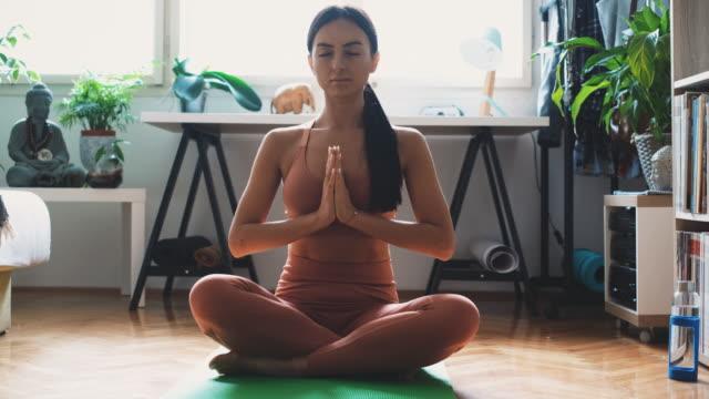 junge frau in sportbekleidung hält hände in namaste geste beim üben meditation und atemübung zu hause. - gebetsposition stock-videos und b-roll-filmmaterial