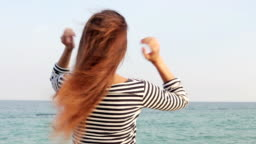 Young woman in striped T-shirt straightens the hair on the beach, view from the back, slow motion