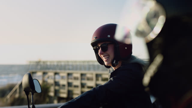 ms slo mo. young woman in sunglasses and motorcycle helmet laughs with friend by oceanfront pier. - ヘルメット点の映像素材/bロール