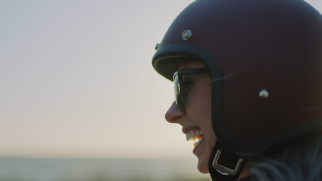 cu slo mo. young woman in sunglasses and motorcycle helmet looks out over the ocean and laughs. - スポーツヘルメット点の映像素材/bロール