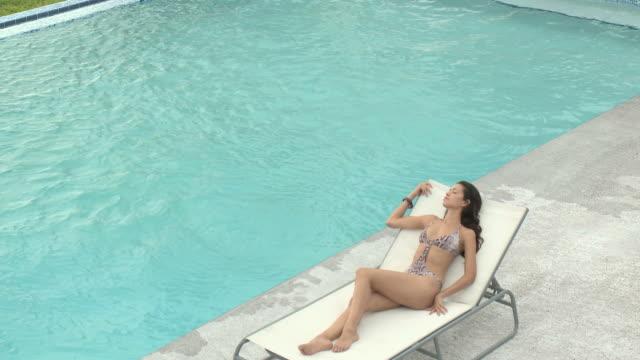 young woman in sunlounger by pool, young man swimming in pool then sitting poolside - badbyxor bildbanksvideor och videomaterial från bakom kulisserna
