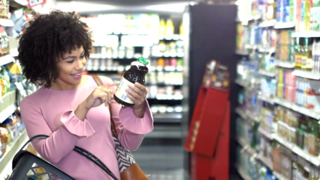 young woman in supermarket reading food label - customer stock videos & royalty-free footage