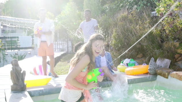 young woman in swimming pool laughing firing watergun at camera - squirt gun stock videos and b-roll footage