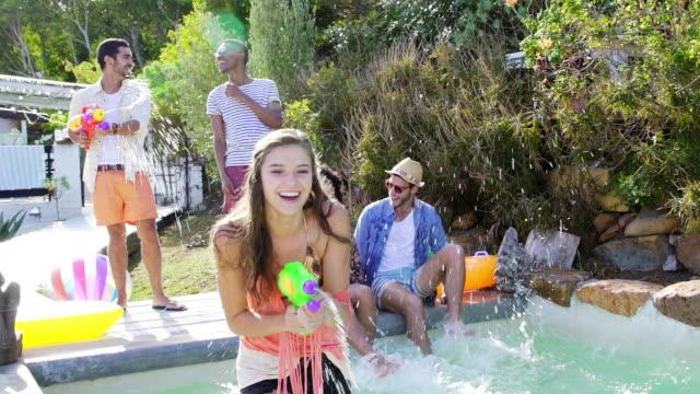 Young woman in swimming pool laughing firing watergun at camera