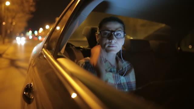 Jonge vrouw in de auto luisteren muziek op de digitale tablet.
