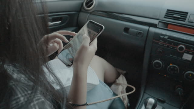 Young woman in the car using the smart phone.