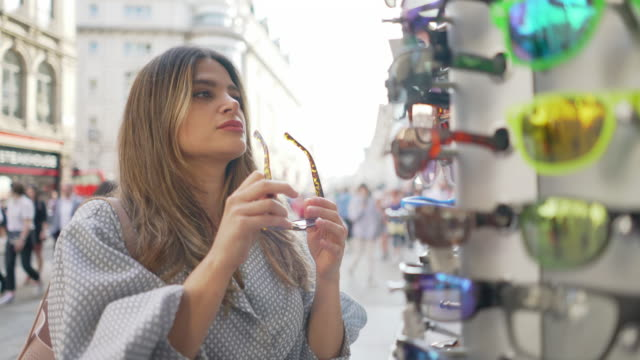 a young woman in the city shopping for sunglasses - sonnenbrille stock-videos und b-roll-filmmaterial