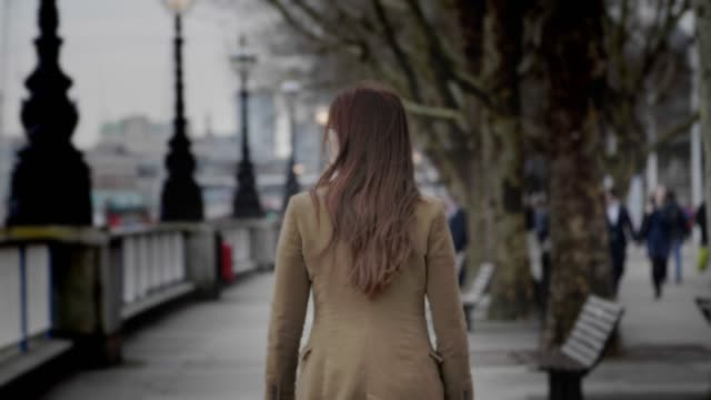 young woman in the city walking away from camera, back view. - homelessness stock videos & royalty-free footage