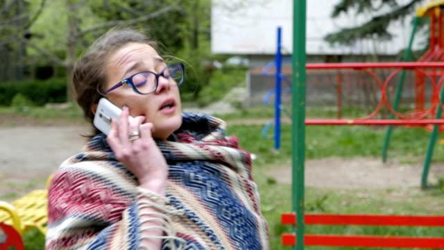 若い女性公園の電話で話している - 電話を切る点の映像素材/bロール