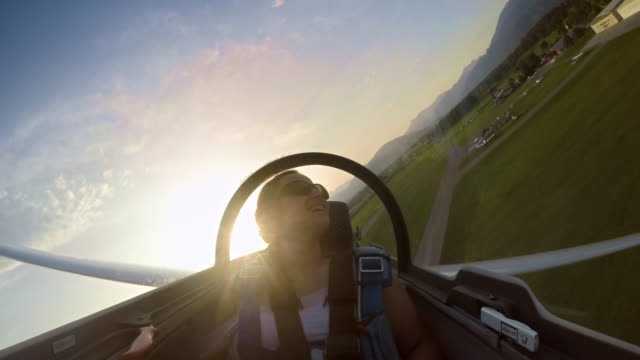 ld young woman in the passenger seat of the glider enjoying the plane gliding low at sunset - gliding stock videos & royalty-free footage