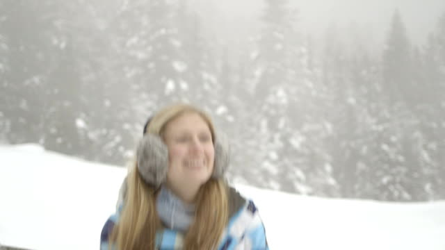 Young woman in the snow wearing earmuffs