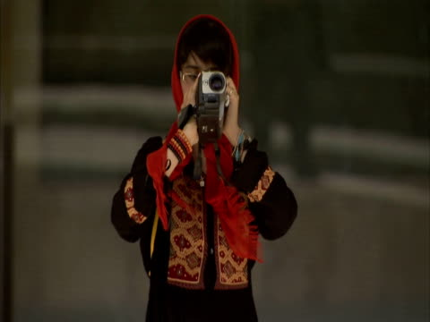 young woman in traditional persian dress pointing camcorder at camera, iran (sound available) - 若い女性だけ点の映像素材/bロール