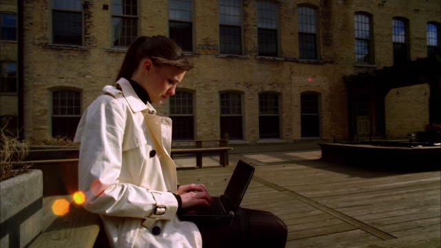ms zi zo ds  young woman in trench coat using laptop / madison, wisconsin, usa - トレンチコート点の映像素材/bロール