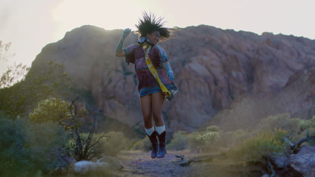 SLO MO. Young woman in vintage dress and boots kicks up dust as she jumps and dances in wild desert landscape.