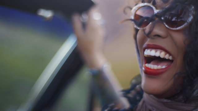vídeos de stock, filmes e b-roll de cu. young woman in vintage shawl and sunglasses laughs in passenger seat of classic convertible on desert highway. - batom