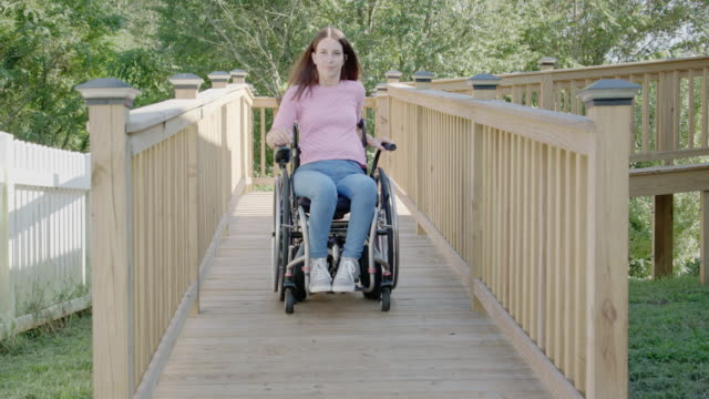 young woman in wheelchair goes down wheelchair ramp - wheelchair stock videos and b-roll footage