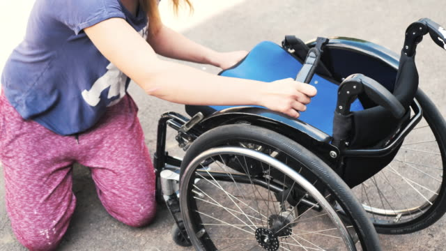 young woman in wheelchair in skate park - preparing wheelchair for stunts - disability services stock videos & royalty-free footage
