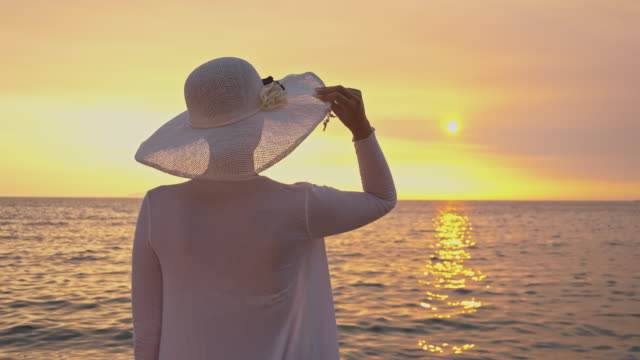 slo mo young woman in white clothes watching the sunset - white shirt stock videos & royalty-free footage