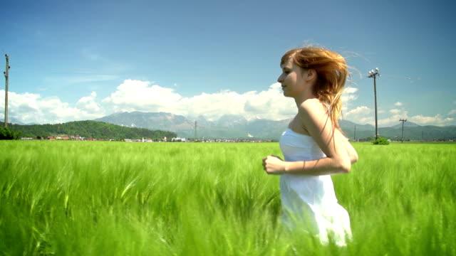 stockvideo's en b-roll-footage met young woman in white dress running through green wheat field - witte jurk