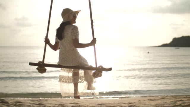 stockvideo's en b-roll-footage met jonge vrouw in witte jurk swingende op het strand - witte jurk