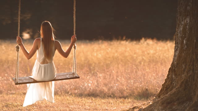 SLO MO TD Young woman in white dress swinging under a big tree