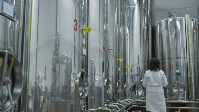 MS TS young woman in white lab coat walking along row of stainless steel tanks, stopping at last tank, looking up and taking notes on clipboard, exits frame right RED R3D 4K