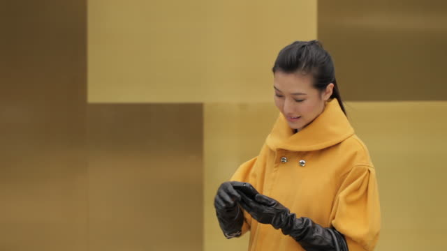 ms young woman in yellow coat using mobile phone and smiling / china - haar nach hinten stock-videos und b-roll-filmmaterial