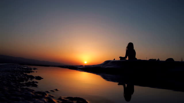 Young woman in yoga lotus position at sunset
