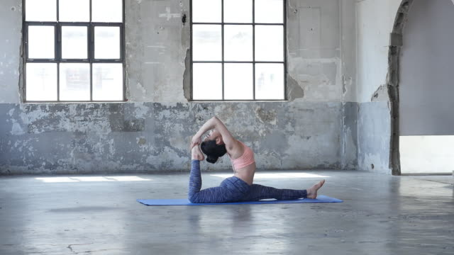 vídeos de stock e filmes b-roll de a young woman in yoga outfit doing splits leg indoors - claraboia