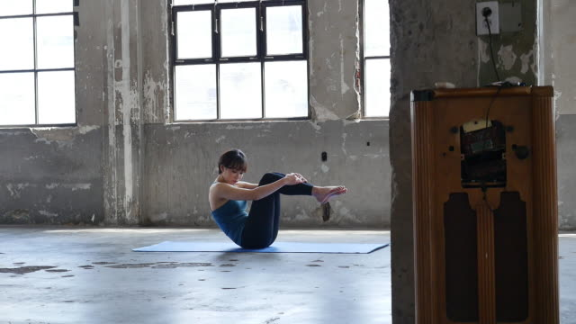 a young woman in yoga outfit doing yoga boat pose indoors - ärmelloses oberteil stock-videos und b-roll-filmmaterial
