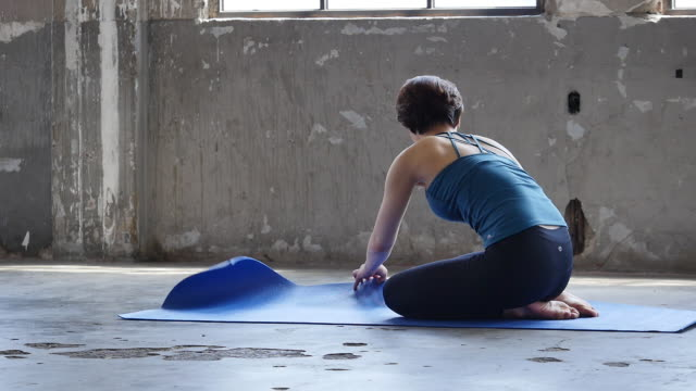 vídeos de stock e filmes b-roll de a young woman in yoga outfit doing yoga downward dog pose indoors - inclinar se pose