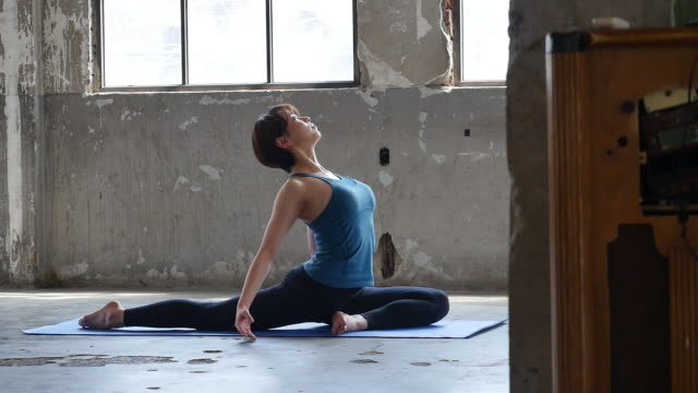 a young woman in yoga outfit sitting and stretching body indoors - ärmelloses oberteil stock-videos und b-roll-filmmaterial